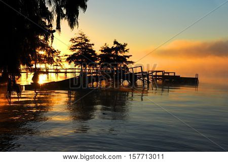 Morning mist hugs a rotting pier on Lake Chicot in Eastern Arkansas. Sunrise tints water orange and yellow.