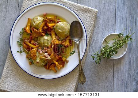 Bread dumplings with chanterelles on a plate with fresh Majoram