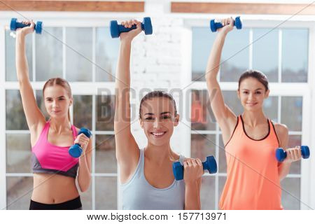 Hands up. Three active young women doing exercises for arms and using dumbbells while spending time in gym.