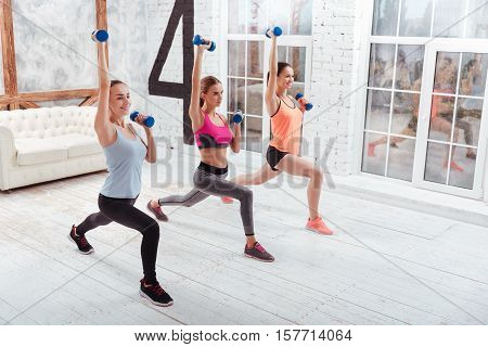 Be active. Three athletic young women doing lunges and using dumbbells while exercising in gym.