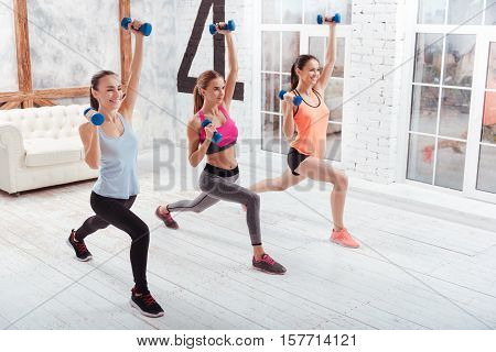 Active life. Three slim young women doing lunges and using dumbbells while training in fitness studio.