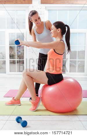 Funny sport. Two active young women training and using fitball while exercising in a gym.