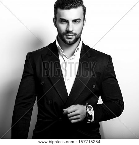 Elegant young handsome man in classic costume. Black-white studio fashion portrait.