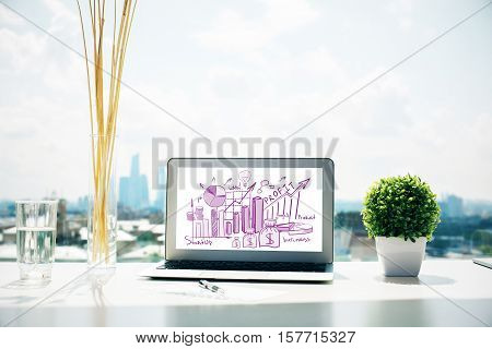 Front view of desktop with business sketch on notebook screen. Finacial report concept