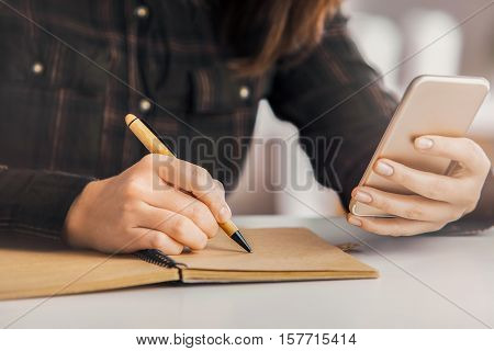 Girl copying infromation from cellphone to notepad. Close up