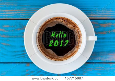 Hello 2017 inscription on top view morning cup of coffee. Happy New Year and Christmas concept.