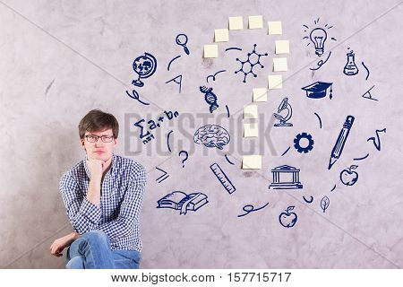 Pensive young man on concrete background with educational sketches and sticker question mark. Confusion concept