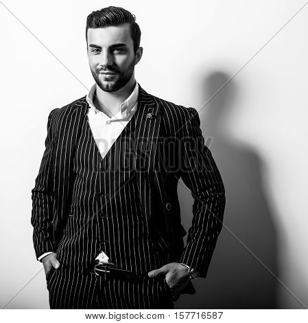 Elegant young handsome man in classic costume. Black-white studio fashion portrait.