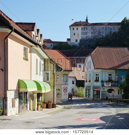 Gmina Škofja Loka, Škofja Loka Slovenia - September 25 2016: Capuchin market. In the background on the hill is visible the Bishops Castle, now the Loka Museum. Two people are visible on the street, also visible is the entrance to the Capuchin Bridge.