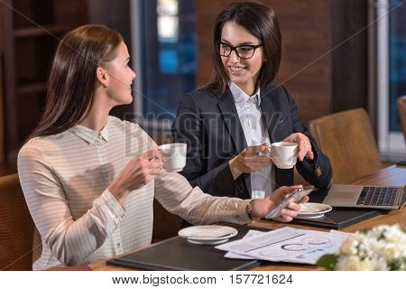 Time for break. Delighted young female colleagues drinking tea while working and making project in an office.