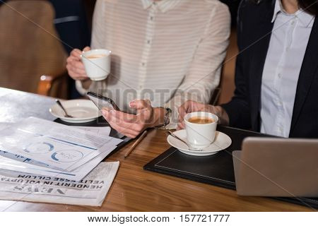 Relaxation is good. Close up of two young female colleagues having a tea break and using smartphone after working in an office.