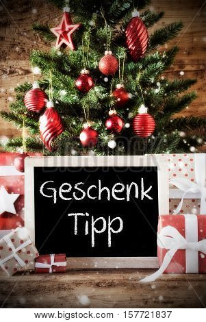 Chalkboard With German Text Geschenk Tipp Means Gift Tip. Christmas Tree With Balls And Snowflakes. Gifts Or Presents In The Front Of Wooden Background With Bokeh Effect
