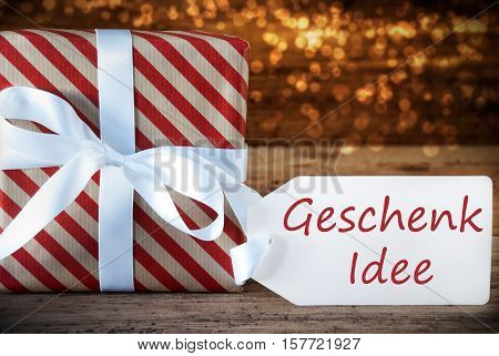 German Text Geschenk Idee Means Gift Idea. Macro Of Christmas Gift Or Present On Atmospheric Wooden Background. Card For Seasons Greetings, Best Wishes Or Congratulations. White Ribbon With Bow.