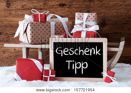 Chalkboard With German Text Geschenk Tipp Means Gift Tip. Sled With Christmas And Winter Decoration. Gifts And Presents On Snow With Wooden Background.