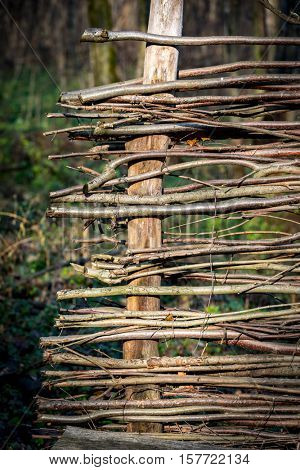 Abstract wooden wattle fence in autumn garden