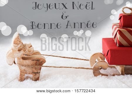 Moose Is Drawing A Sled With Red Gifts Or Presents In Snow. Silver Background With Bokeh Effect. French Text Joyeux Noel Et Bonne Annee Means Merry Christmas And Happy New Year