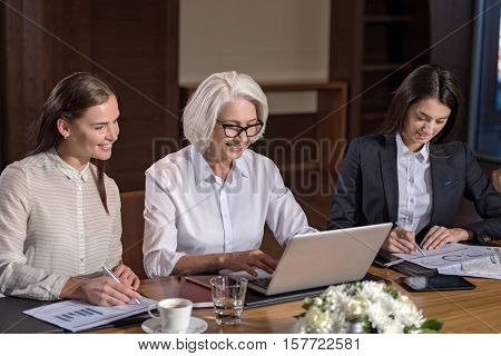 Best company. Two young female colleagues and their elderly boss working together and using laptop and documents while sitting in an office.