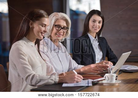 Friendly workers. Pretty young female colleagues and their experienced boss working together and making project while sitting in an office.