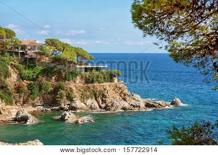 Luxury modern house on the cliff rock in the edge. Bay and crystal clear water of Mediterranean Sea. Amazing blue green sea and sunny day.