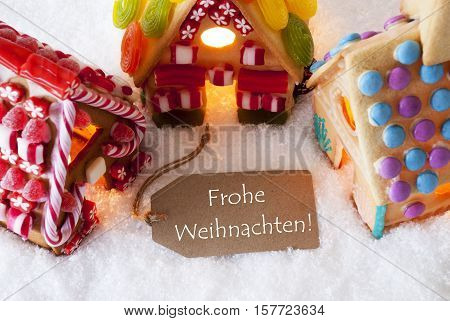 Label With German Text Frohe Weihnachten Means Merry Christmas. Colorful Gingerbread House On Snow. Christmas Card For Seasons Greetings