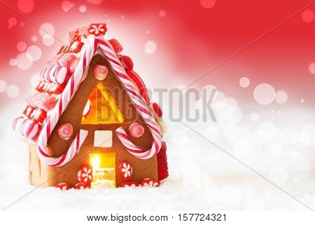 Gingerbread House In Snowy Scenery As Christmas Decoration. Candlelight For Romantic Atmosphere. Red Background With Snowflakes. Copy Space For Advertisement Or Free Text
