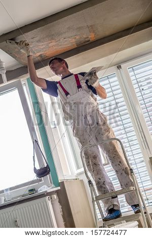 Thirty years old manual worker with wall plastering tools renovating house. Plasterer renovating indoor walls and ceilings with float and plaster. Wall mash installation. Construction finishing works.