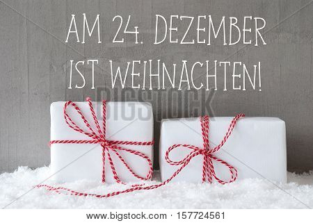 German Text Am 24. Dezember Ist Weihnachten Means December 24th Is Christmas Eve. Two White Christmas Gifts Or Presents On Snow. Cement Wall As Background. Modern And Urban Style.