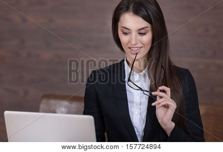 Pretty young ambitious woman holding documents and glasses while posing and standing in the office.
