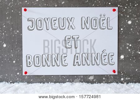 Label With French Text Joyeux Noel Et Bonne Annee Means Merry Christmas And Happy New Year. Urban And Modern Cement Wall As Background On Snow With Snowflakes.