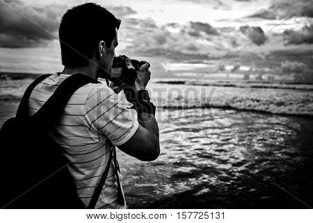 Photographer traveler photographs a sunset over ocean. Black-white photo with copy-space.