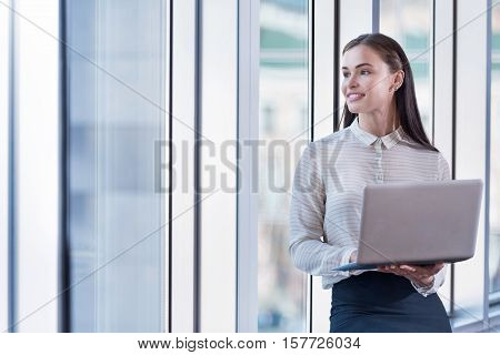 Always in touch. Brunette young pretty woman using laptop while standing near the window and working in an office.
