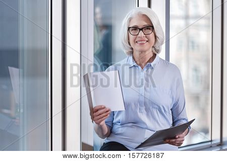 Experienced and professional. Elderly elegant delighted woman posing with documents while sitting in an office and working.