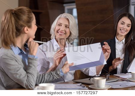 Workaholic dream. Three female ambitious colleagues enjoying conversation about work and smiling while sitting in an office.