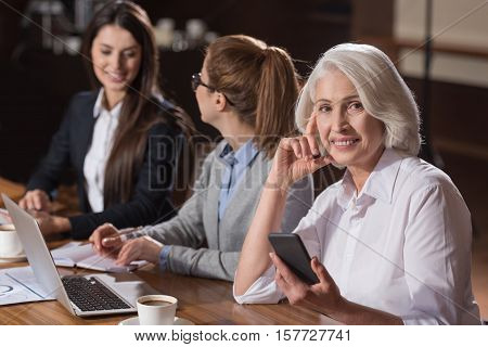 Different generations. Elderly elegant delighted woman posing with her young colleagues while they working and talking in an office.