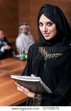 Feeling happiness. Young pretty business woman in black robe standing in the office writing some information into the documents with a happy look