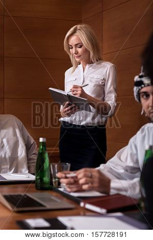 Be attentive. Pretty intent young woman standing near the table between Arabian men holding the notebook and the pen in her hands carefully listening and writing down the facts