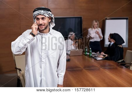 Keep in touch. Positively delighted businessman wearing the white robe and keffiyeh on his head looking aside and making a telephone call during the break.