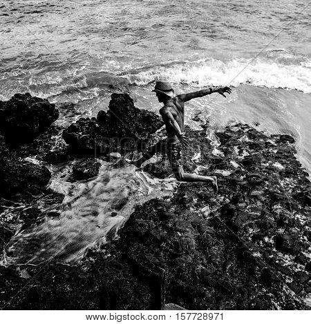 Man travaler jumps from beach stones. Black-White photo.