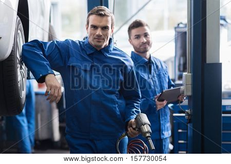 Ucse it smartly.Confident professional car mechanic hoding pneumatic car wrench and going to change the wheel while his colleague standing in the background
