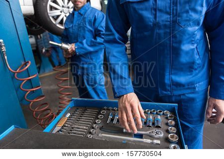 hat to choose. Pleasant professional mechaic standing near set with tools and choosing a correct one while going to repair the car with his colleague