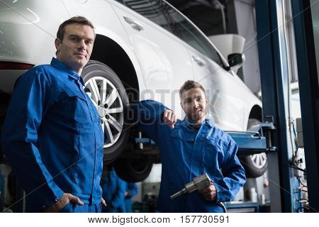 We will do it. Pleasant professional car mechanics standing near car and going to repair it while using pneumatic wrench