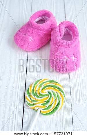 baby's bootees and candy on wooden background.