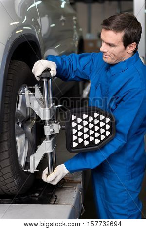 Involved in work.Professional young mechanic standing near car and adjusting automobile wheel alignment while being involved in work