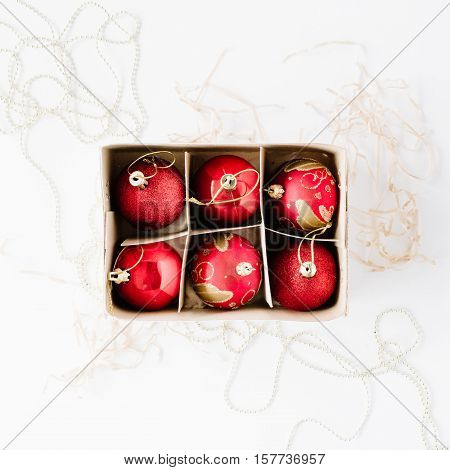 box with bright red christmas balls on white background. flat lay top view