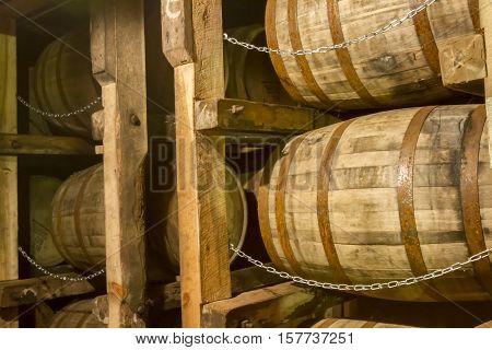 Bourbon barrels inside rik or rack house warehouse.