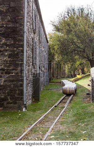 Oak barrels on rails outside stone bourbon distillery.