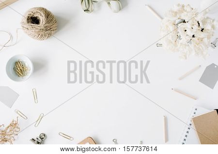Flat lay top view office table desk. feminine desk workspace frame with twine pencils floral bouquet craft diary and clips on white background.