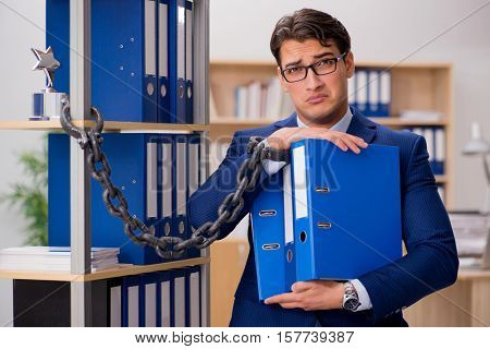 Handsome businessman chained to the office shelf