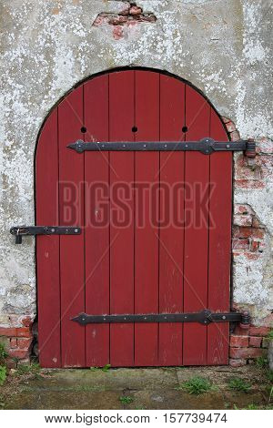 Red wooden arched medieval door with lock