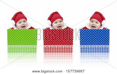 Asian baby cute and smile wearing Santa Claus suit playing in the open red gift box green gift box and blue gift box set for surprise on Christmas and Happy New Year day isolated on white